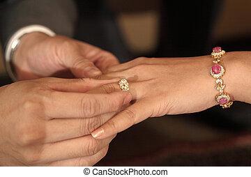 groom putting a wedding diamond ring on bride 's finger