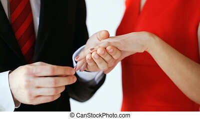 groom putting a wedding ring to bride hand
