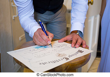 Groom Signing Marriage Certificate - A groom signs the...