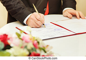 Groom signing marriage wedding contract
