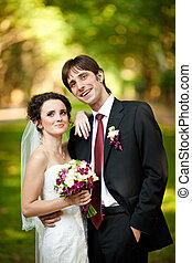 Groom smiles sincerely while bride holds her hand on his shoulder