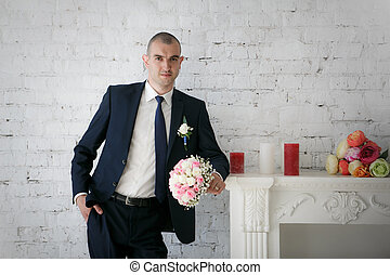 groom standing near fireplace with wedding bride bouquet