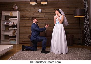 Groom standing on his knees against happy bride
