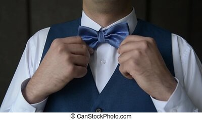 groom straightens bow-tie on shirt