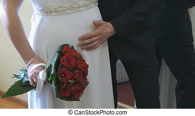 Groom strokes the stomach of his pregnant wife