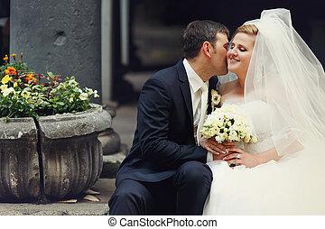 Groom tells bride a secret - newlyweds seat behind an old stone flowerbed