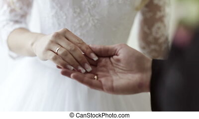 Groom tenderly holds the hand of the bride