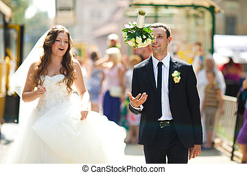 Groom throws a bouquet while walking with a bride