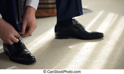 Groom tie shoelaces on black shoes at home before visiting bride