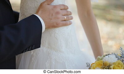 Groom touch his bride on waist and hip, close up