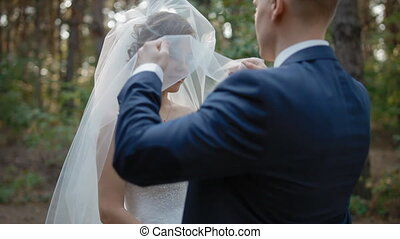 Groom up the veil of his bride