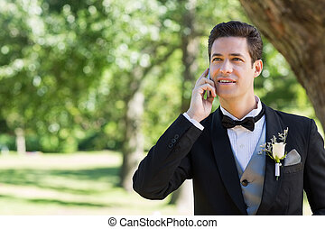 Groom using cellphone in garden