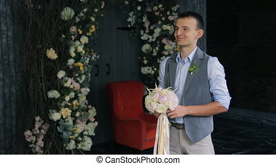 Groom waits for bride to hand her wedding bouquet. Man...