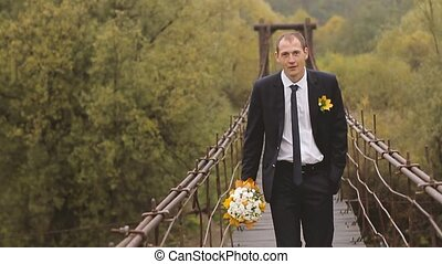 Groom Walking Through the Wooden Bridge in the Mountains