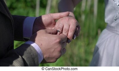 Groom wearing wedding ring to his bride outdoors