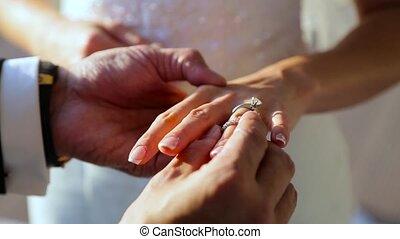 Groom wears a bride a wedding ring