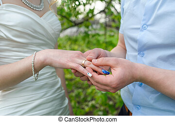 groom wears bride a gold ring on his finger in the garden