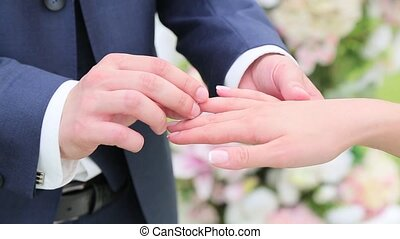 Groom wears ring on the bride's finger