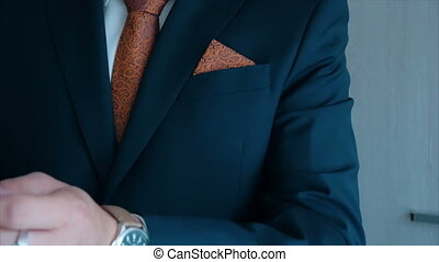 groom wears watch on his left hand at wedding.