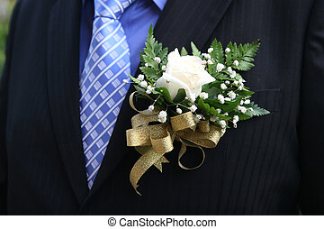 Groom - White rose boutonniere on the lapel of a groom.