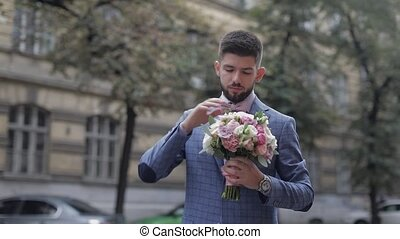 Groom with a black beard with wedding bouquet on the street. Wedding day