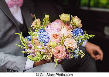 Groom with bouquet in the wedding car