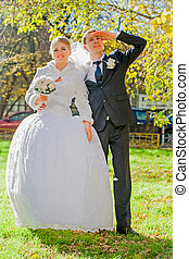 Groom with bride are looking ahead. Sunny autumn.