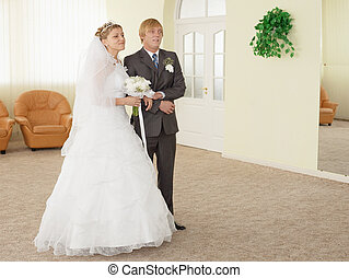 Groom with bride in ceremonial hall