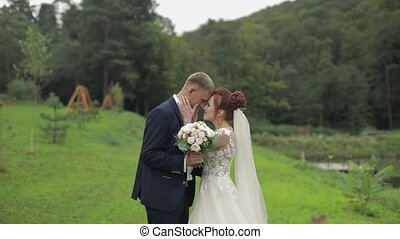Groom with bride near lake in the park. Wedding couple. Slow motion