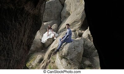 Groom with bride sit on a high slope of the mountain. Wedding couple. Happy