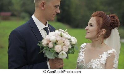 Groom with bride walking near lake in the park. Wedding couple. Slow motion