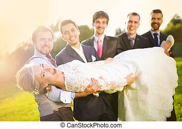 Groom with his friends holding bride