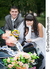 groom with the bride near the wedding car