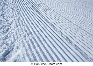 Groomed ski run track in snow