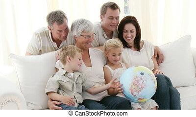 groot, gezin, op, sofa, kijken naar, een, aardze globe