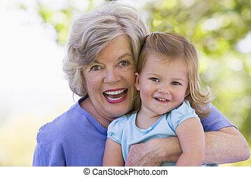 grootmoeder, het glimlachen, kleindochter