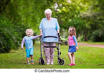 grootmoeder, met, walker, spelend, met, twee, geitjes