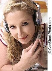 Listening to music through headphones.