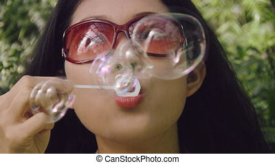 Groovy girl blows rainbow bubbles. - Sexy asian woman...