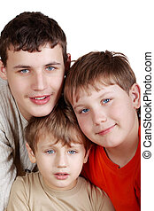 gros plan, coloré, âges, différent, trois, garçons, sourire, t-shirts.