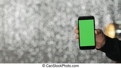 gros plan, smartphone, tenue, écran, main, arrière-plan vert, homme, argent, paillette
