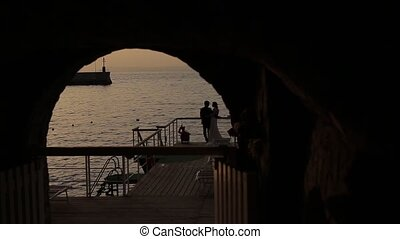 Grotto at the sea at sunset, the bride and groom