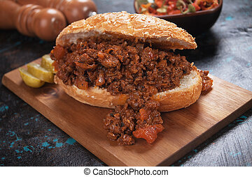 Ground beef sandwich served on wooden board