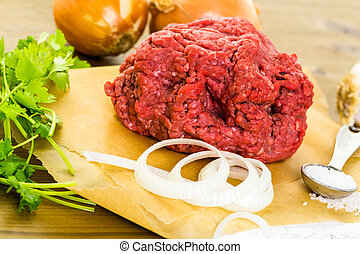 Ground beef on the table with other ingredients for recipe.