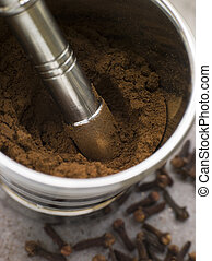 Ground Clove Powder in a Pestle and Mortar