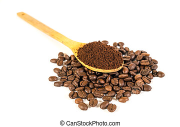 Ground coffee on wooden spoon. Lots of coffee beans scattered on