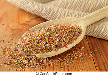 Coarsely ground organic flax seed in a wooden spoon.