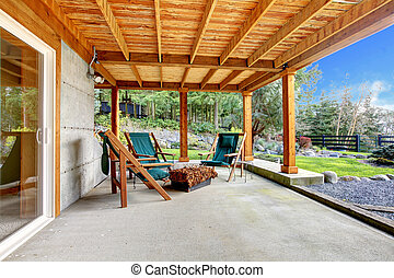 Ground level deck with chairs and door with wood ceiling.