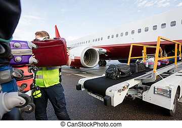 Ground Member Stacking Bags On Trailer At Runway - Mid adult...