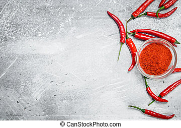 Ground pepper in a glass bowl and fresh red pepper with rosemary.